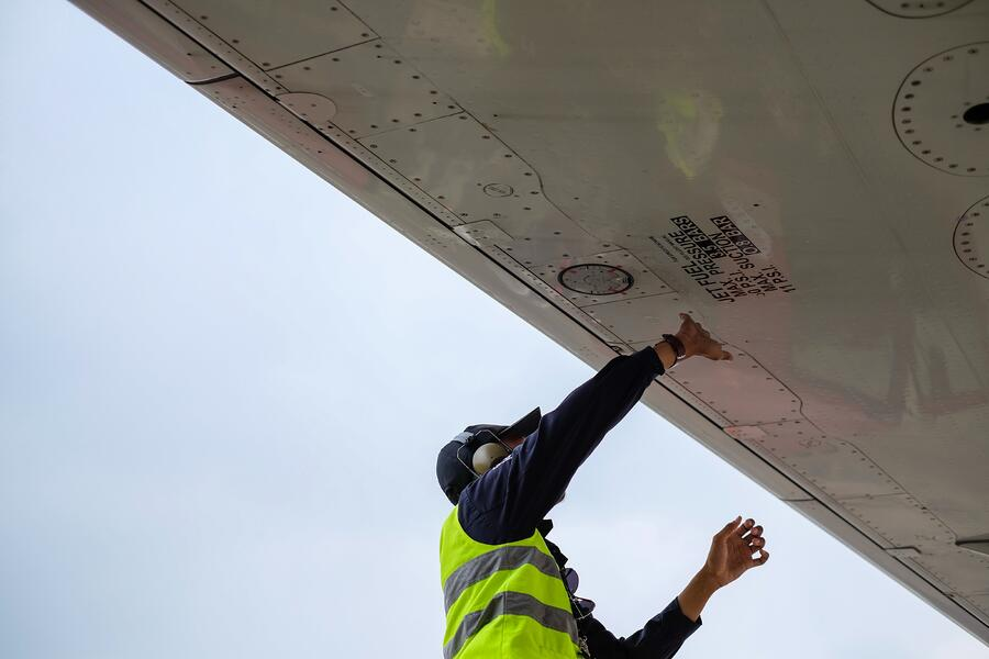 Source One Spares Understanding MSG-3 Aviation Maintenance Guy Inspecting Airplane Wing